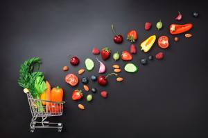 Shopping trolley filled with fresh organic vegetables, fruits and berries on black chalkboard. Top