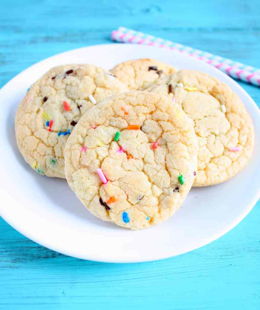 Four cake mix cookies on a white plate. Two striped straws rest in the background.