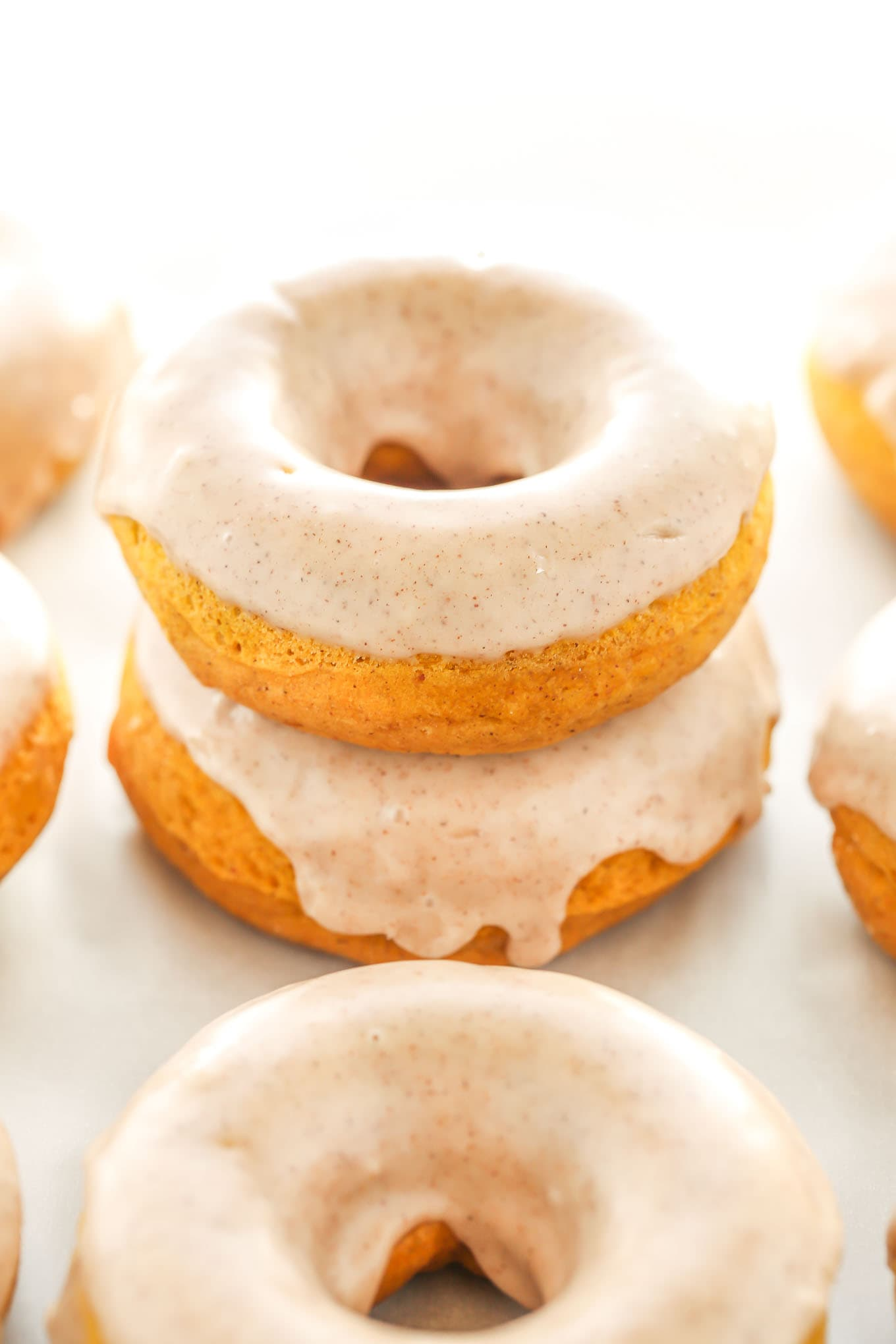An easy recipe for baked pumpkin donuts topped with maple cinnamon glaze. Perfect for an easy and delicious fall breakfast!