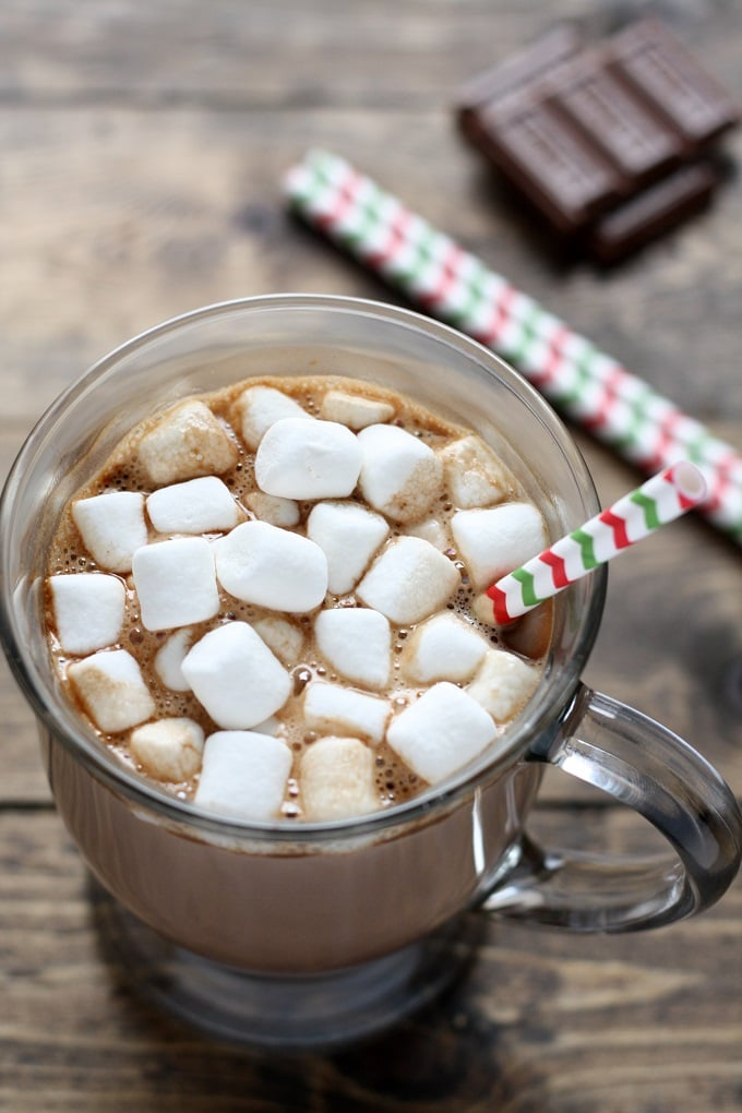 Mug of homemade hot chocolate topped with mini marshmallows and a straw. Chocolate squares rest in the background.