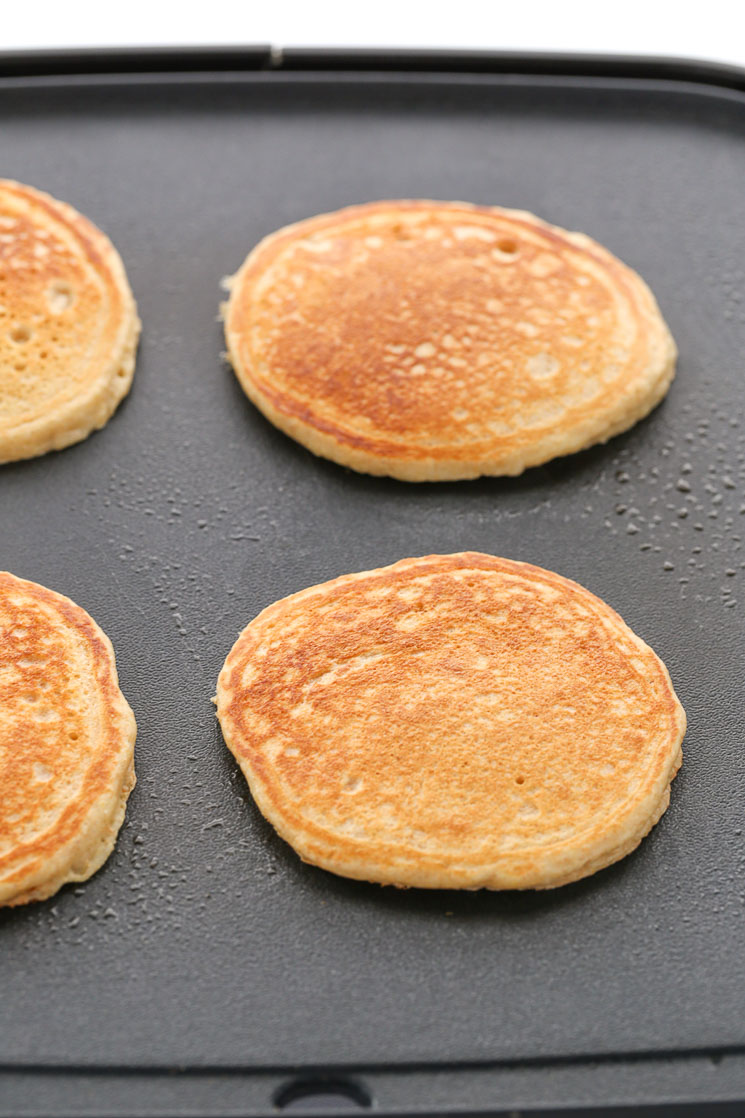 A black griddle topped with four fully cooked whole wheat pancakes.