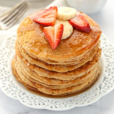 A stack of whole wheat pancakes topped with strawberry, banana slices, and maple syrup.