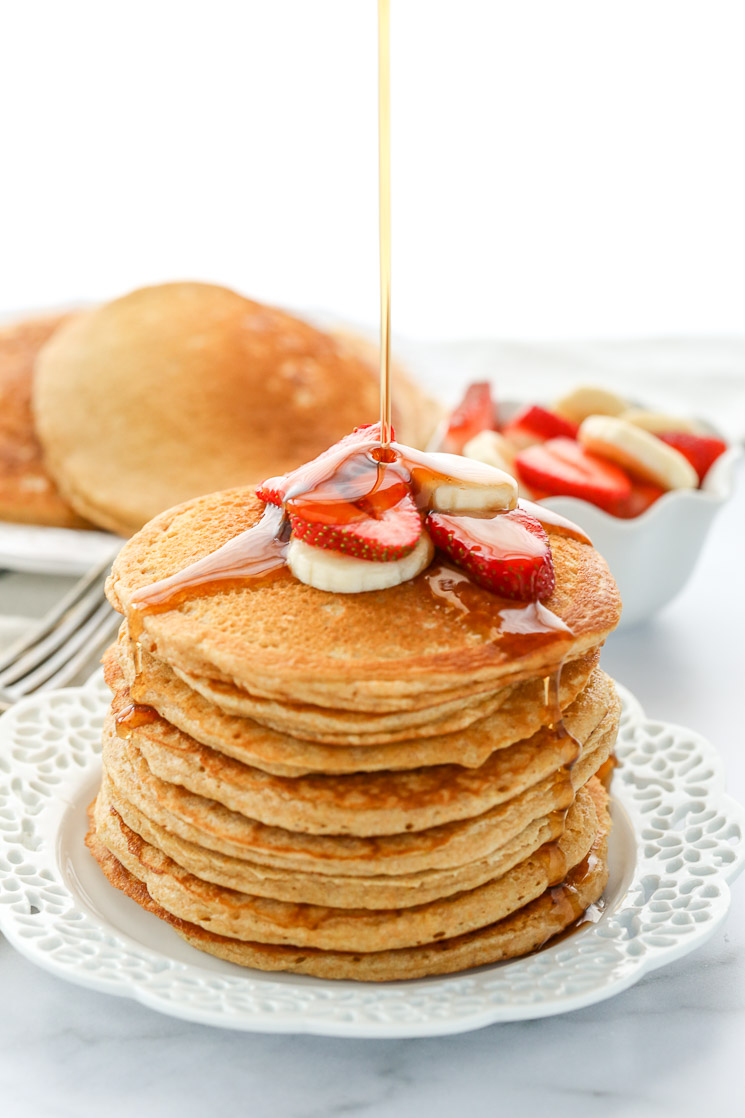 A stack of whole wheat pancakes topped with sliced strawberries and bananas drizzled with pure maple syrup.