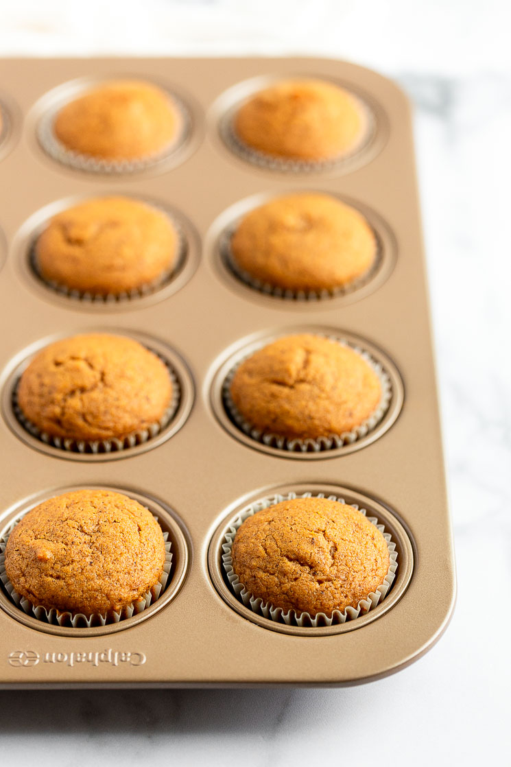 A muffin pan filled with pumpkin cupcakes fresh out of the oven.