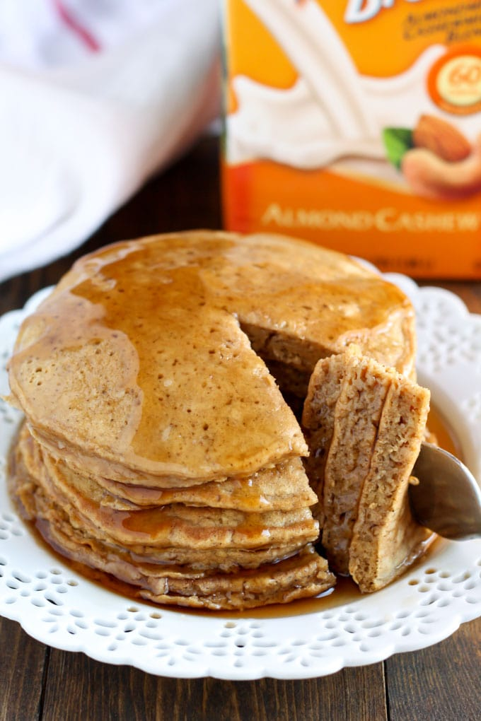 Stack of gingerbread pancakes on a white plate. A bite has been cut out.