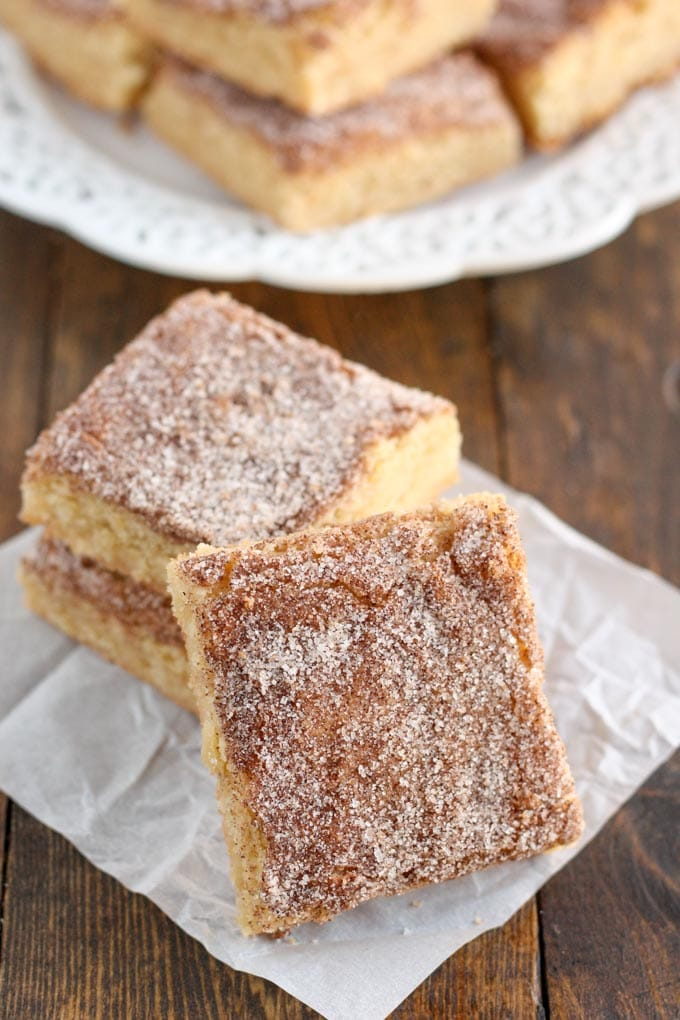Three snickerdoodle bars on a square of parchment paper. More bars are piled on a white plate in the background.