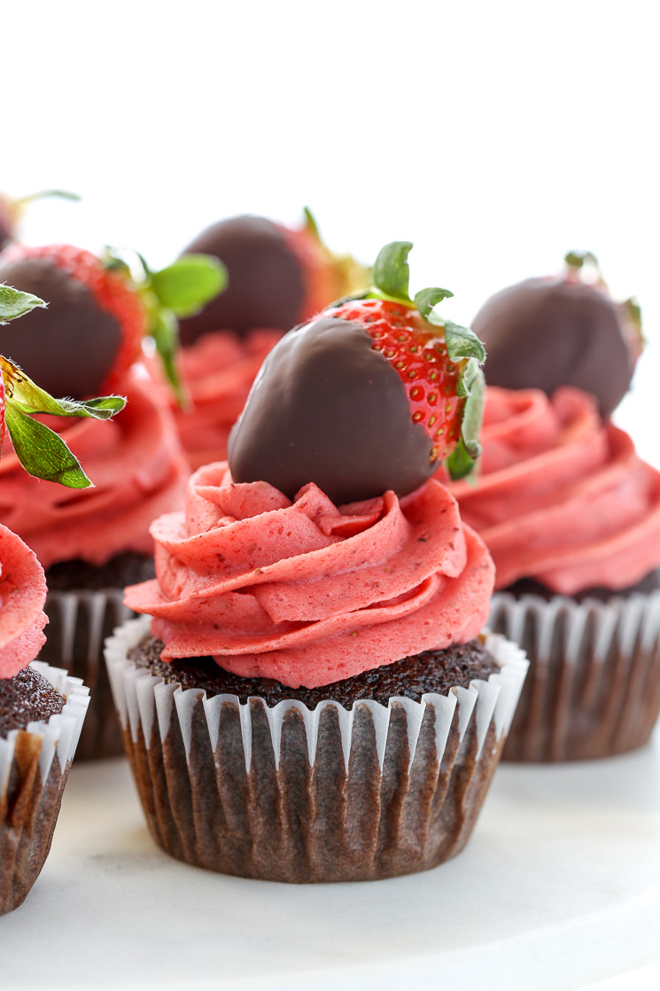A closeup shot of chocolate cupcakes topped with strawberry buttercream frosting and chocolate covered strawberries on a white marble cake stand.
