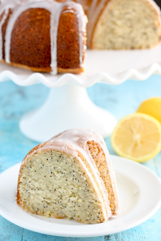 A slice of glazed lemon poppy seed bundt cake on a white plate. The rest of the cake is on a cake stand in the background.