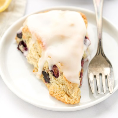 A closeup shot of a lemon blueberry scone on a white plate with a fork on the side.