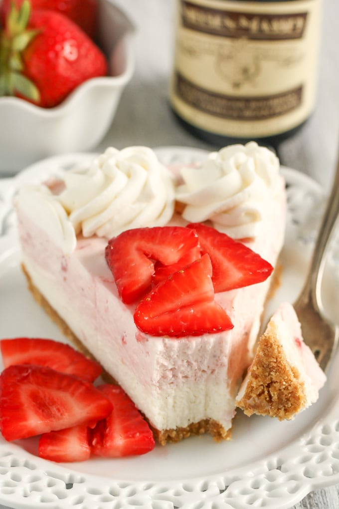 A slice of no bake strawberry cheesecake on a white dessert plate with berry slices and a fork. A bottle of vanilla extract rests in the background.