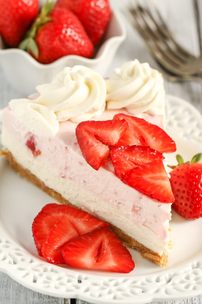 A slice of no bake strawberry cheesecake on a white dessert plate with berry slices. A dish of berries and a fork rest in the background.