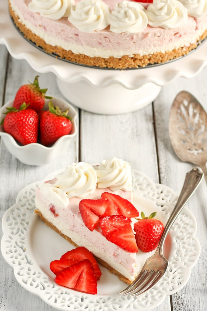 This No-Bake Strawberry and Vanilla Bean Cheesecake starts with a homemade graham cracker crust and is topped with a no-bake vanilla bean cheesecake layer, strawberry cheesecake layer, and a homemade vanilla bean whipped cream!