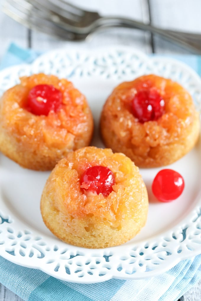 Three mini pineapple upside down cakes on a white dessert plate. A fork rests in the background.