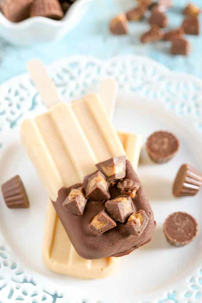 Peanut butter popsicles topped with magic shell and mini peanut butter cups. These Peanut Butter Cup Pudding Pops are a delicious and easy summer treat!