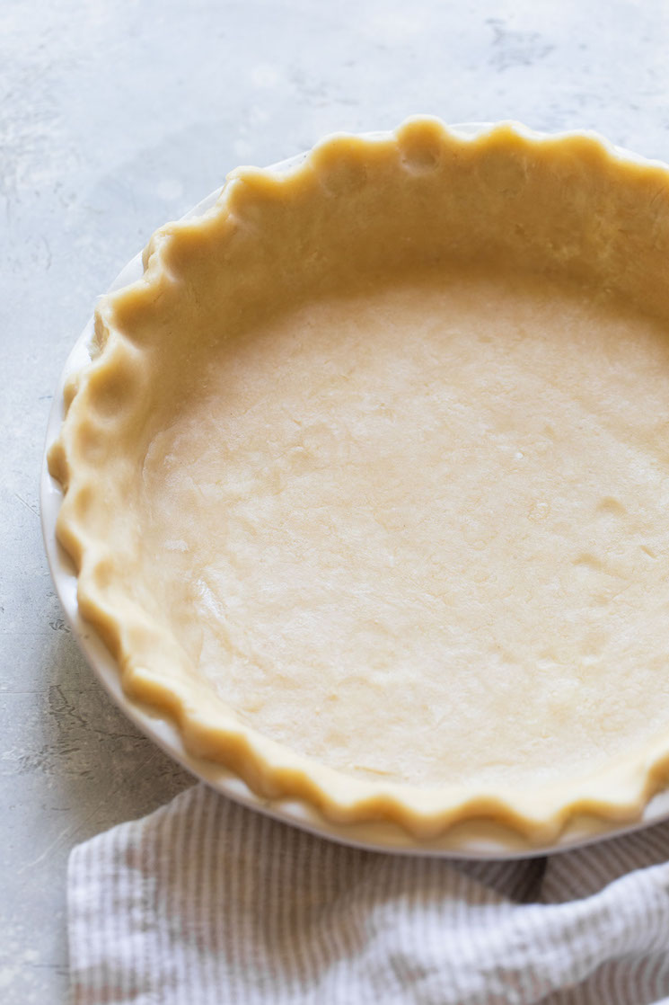A finished unbaked pie crust showing the decorated edge.
