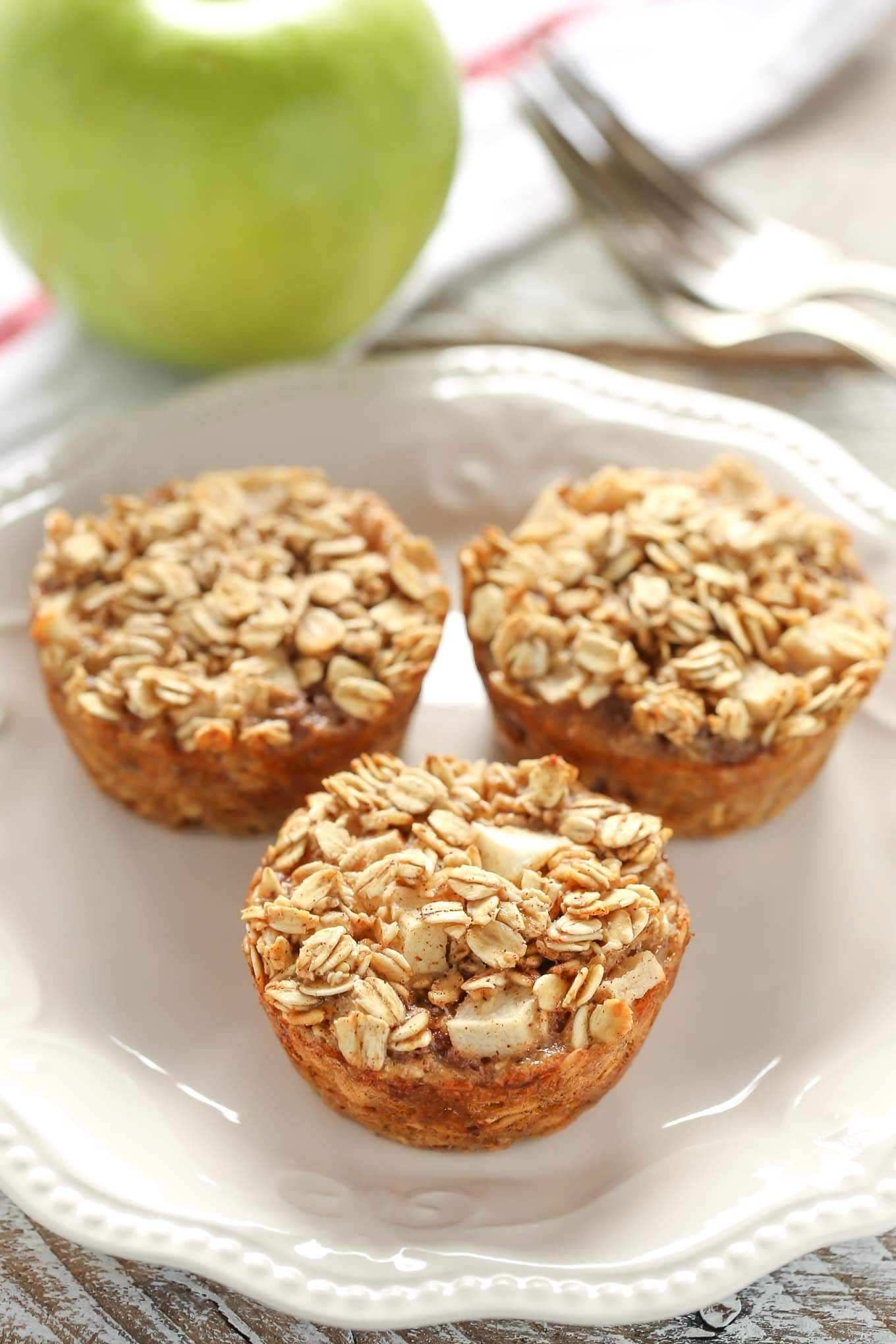 Three baked apple oatmeal cups on a white plate. A Granny Smith apple rests in the background on a tea towel.