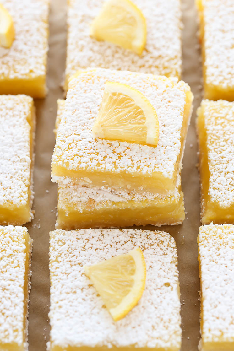 Sliced lemon bars with lemon slices on each one sitting on top of a piece of parchment paper.