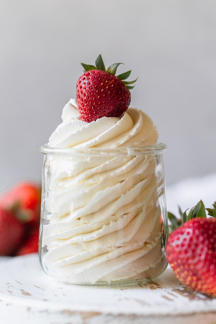 A small glass jar filled with homemade whipped cream topped with a strawberry.