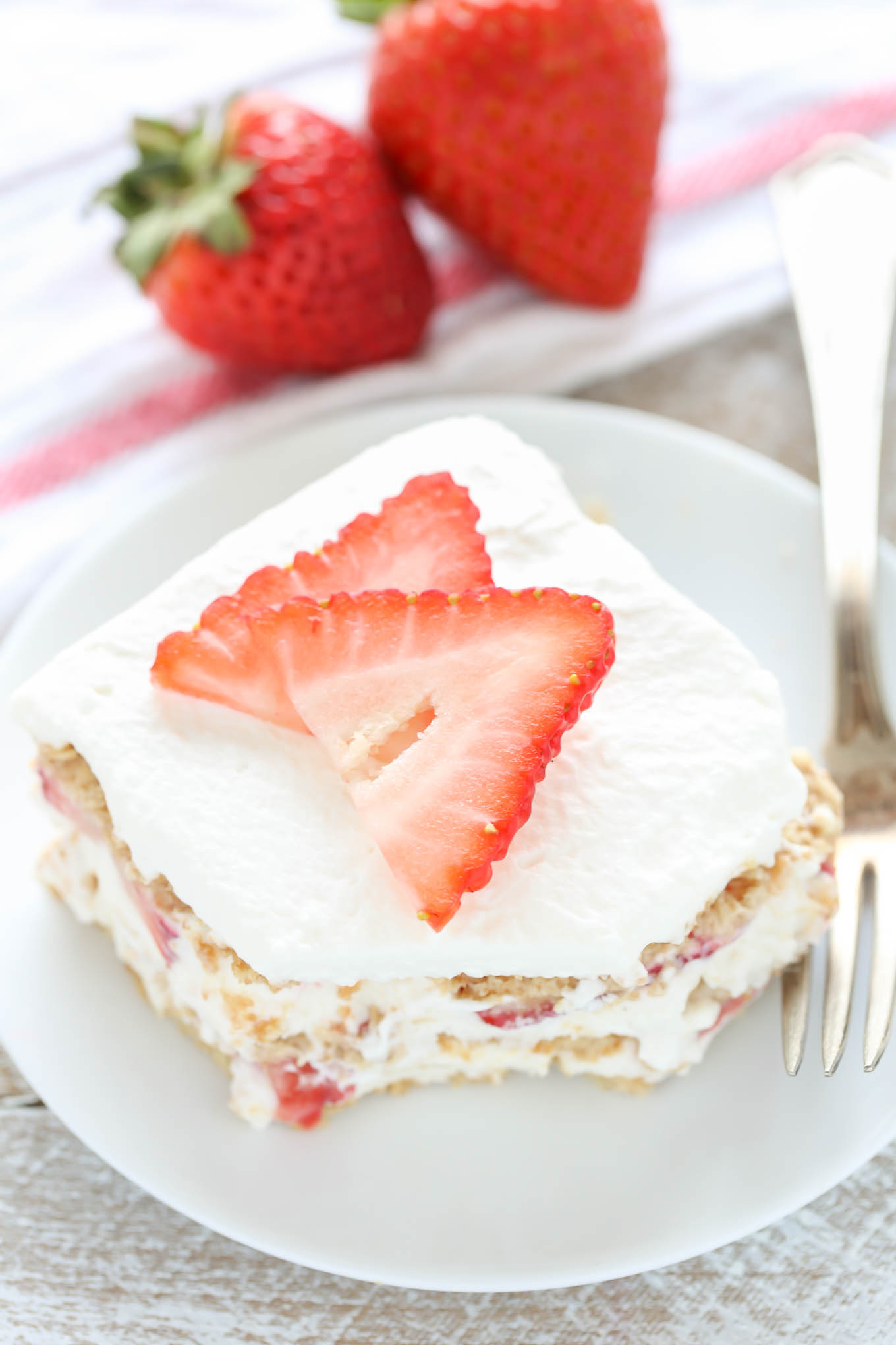 A slice of strawberry graham cracker icebox cake on a white plate with a fork. Two fresh berries rest in the background on a towel.