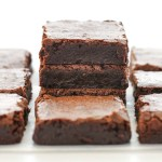 A stack of sliced brownies on parchment paper with more brownies around it.