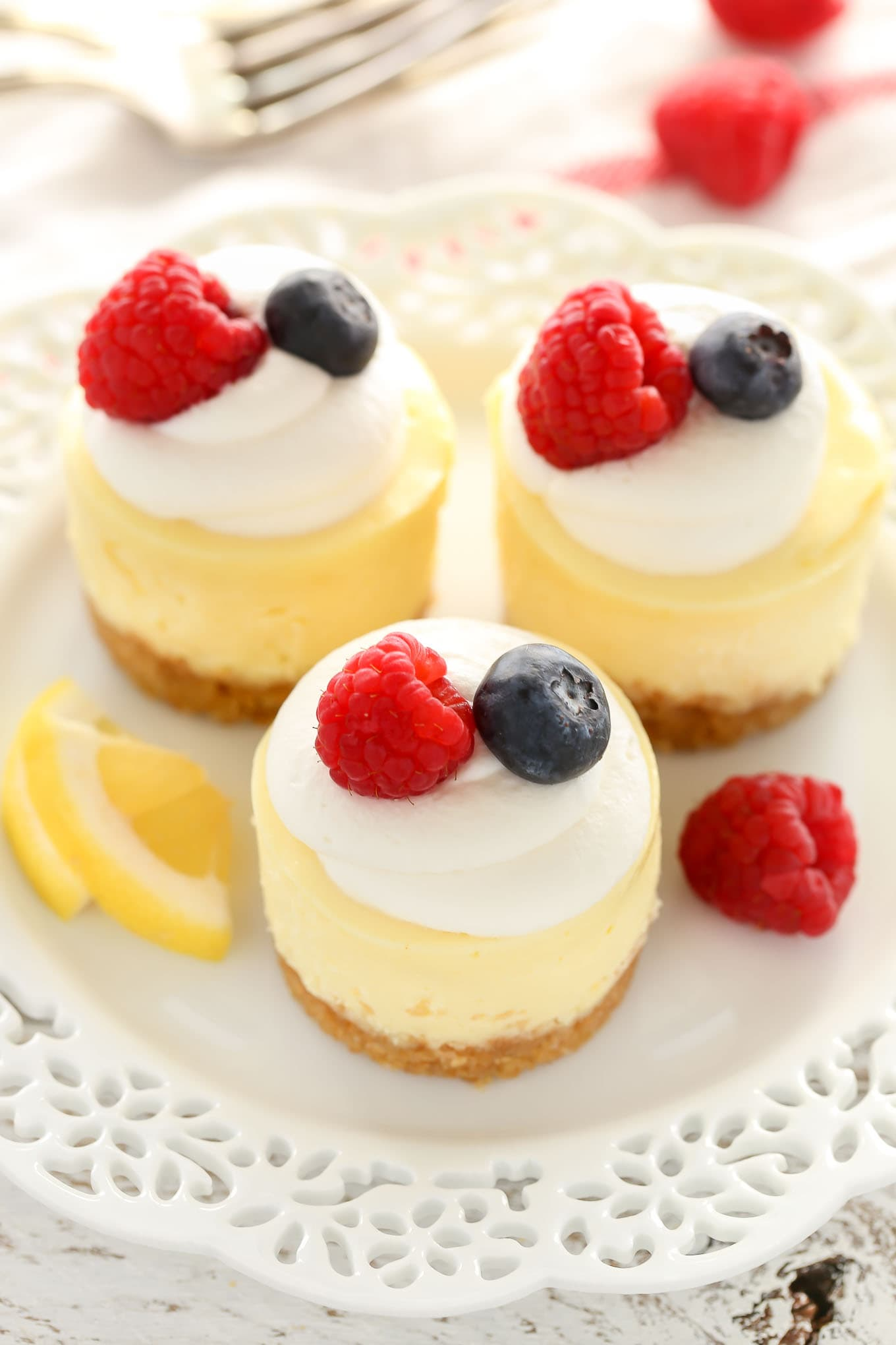 Overhead view of three mini lemon cheesecakes garnished with whipped cream and berries on a white plate. A fork rests in the background.