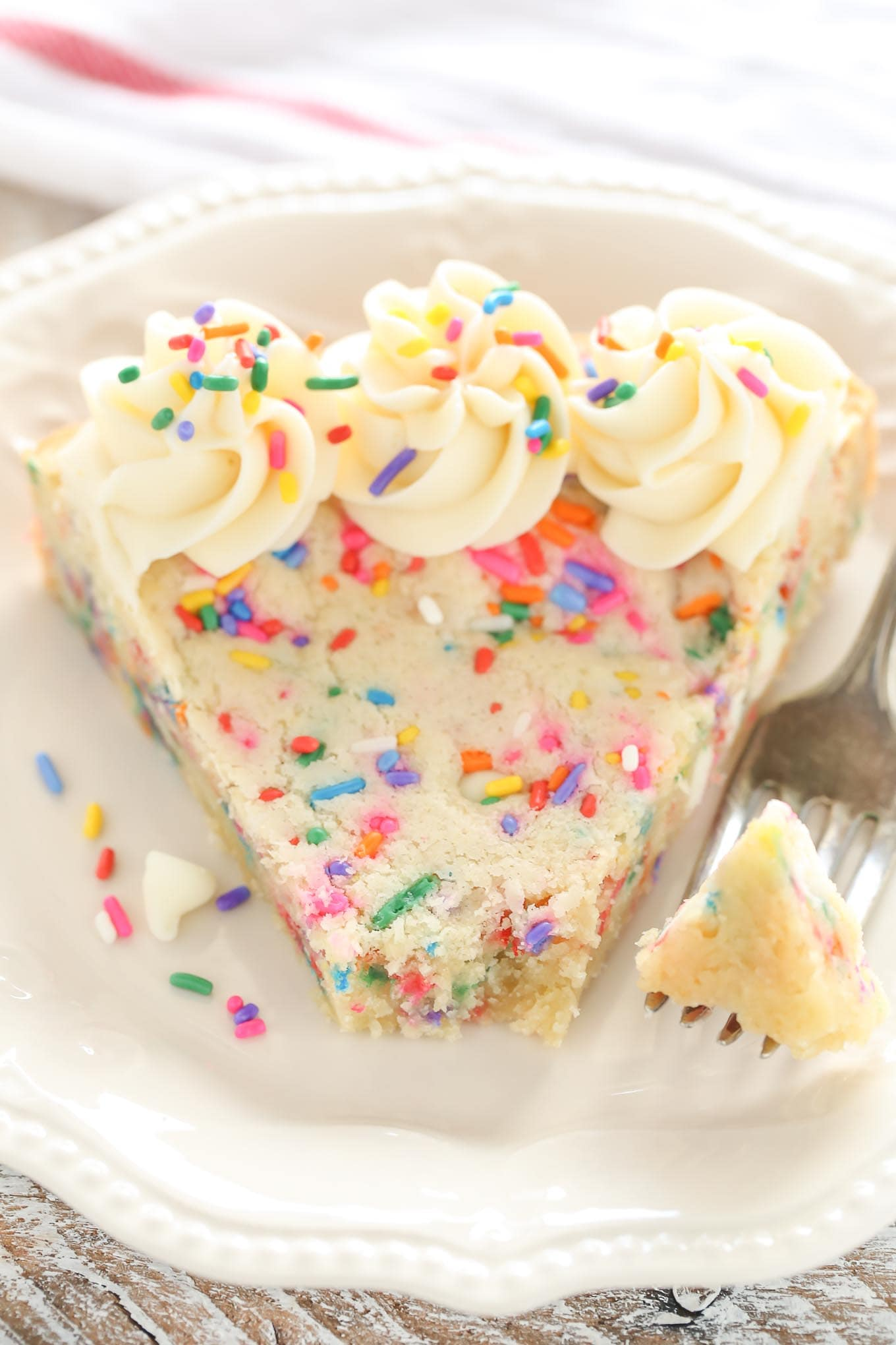 A sugar cookie cake with sprinkles, white chocolate chips, and topped with a homemade vanilla frosting.  This Funfetti Sugar Cookie Cake is easy to make and a perfect dessert for any occasion!