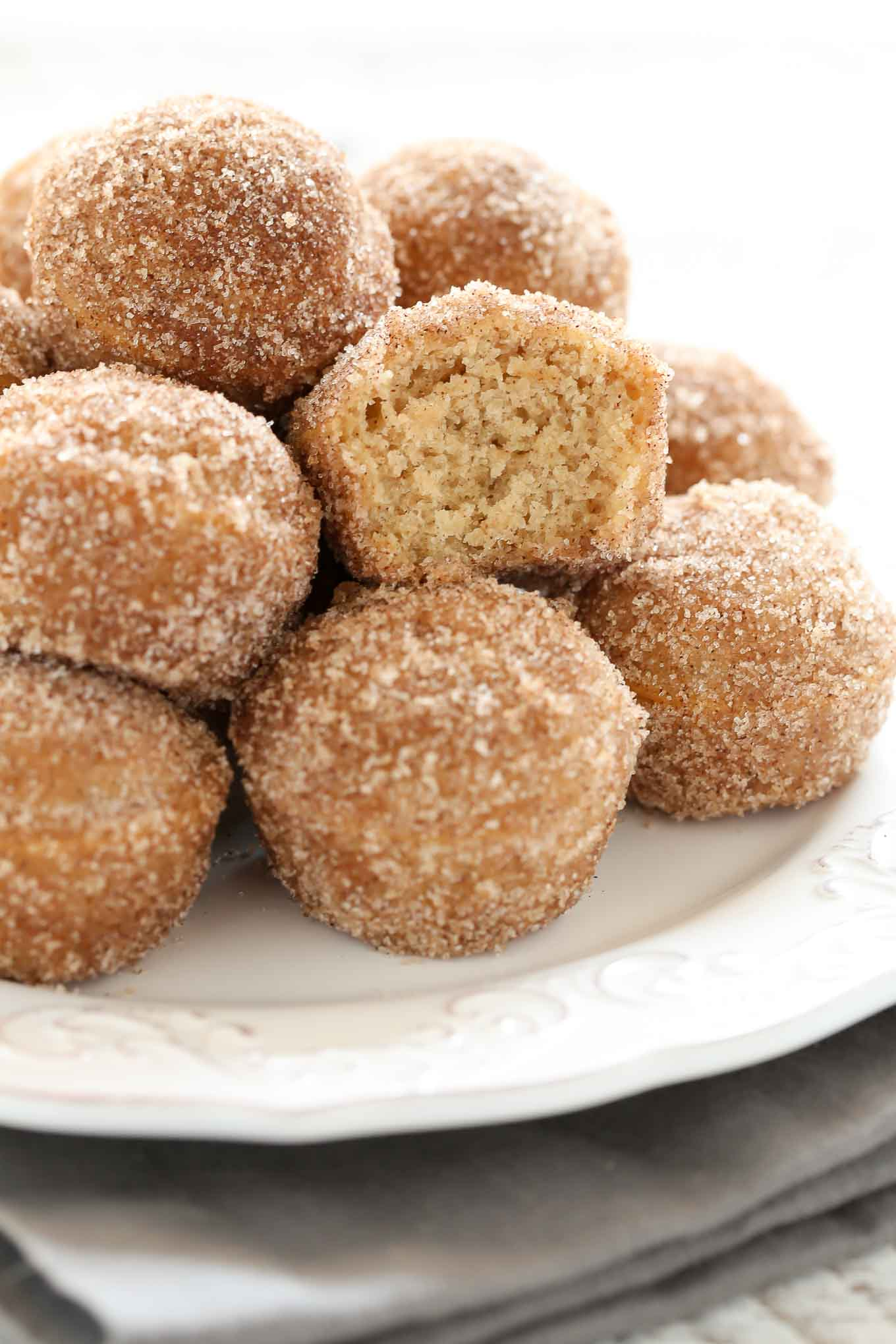 Close up shot of pile of cider donut holes on a white plate. The middle donut hole has a bite missing.