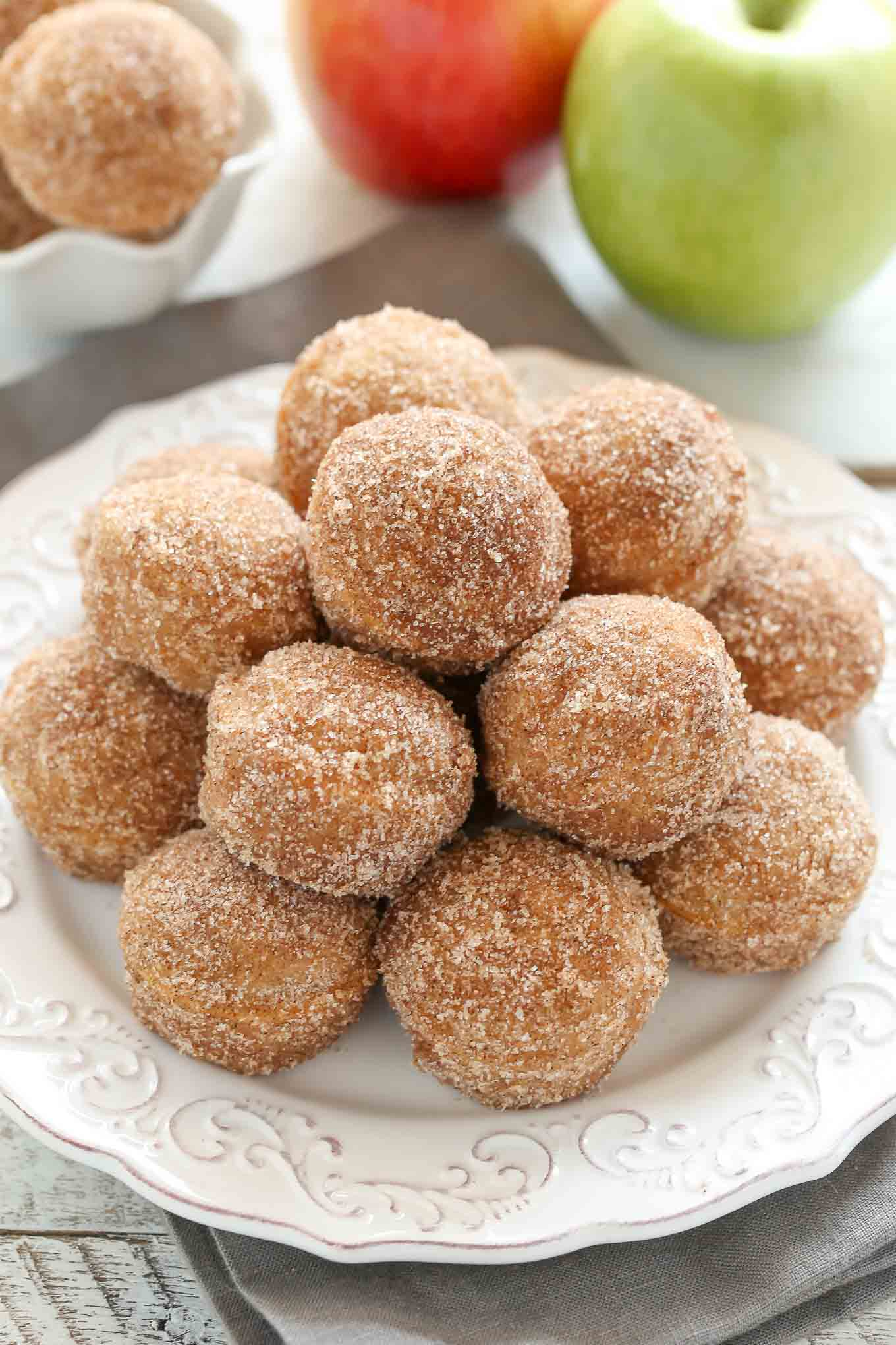 A white plate piled high with apple cider donut holes. Two apples rest in the background.