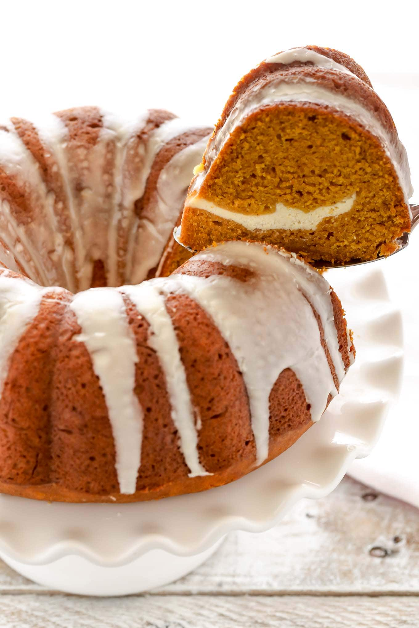 A slice of pumpkin spice bundt cake being removed from a cake stand.