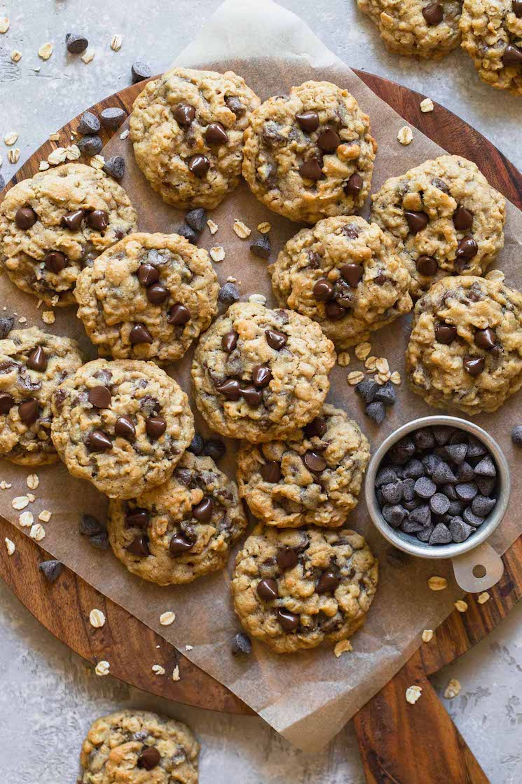 A wooden tray with oatmeal chocolate chip cookies on parchment paper with oats and chocolate chips scattered around them.