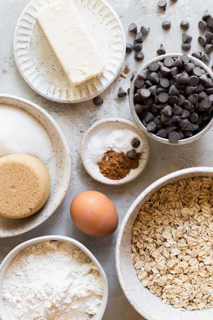 The ingredients needed to make oatmeal chocolate chip cookies separated onto speckled bowls and plates.