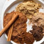 Several different spices separated on a white plate. Two cinnamon sticks rest on top of the ground cinnamon.