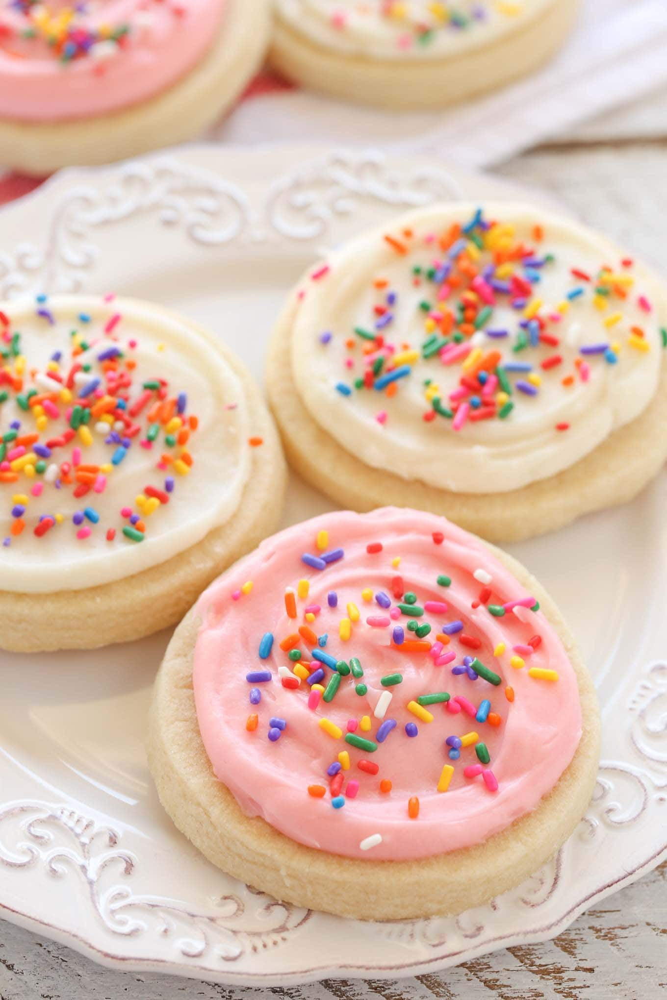 Three frosted sugar cookies on a white plate. Additional sugar cookies rest in the background.