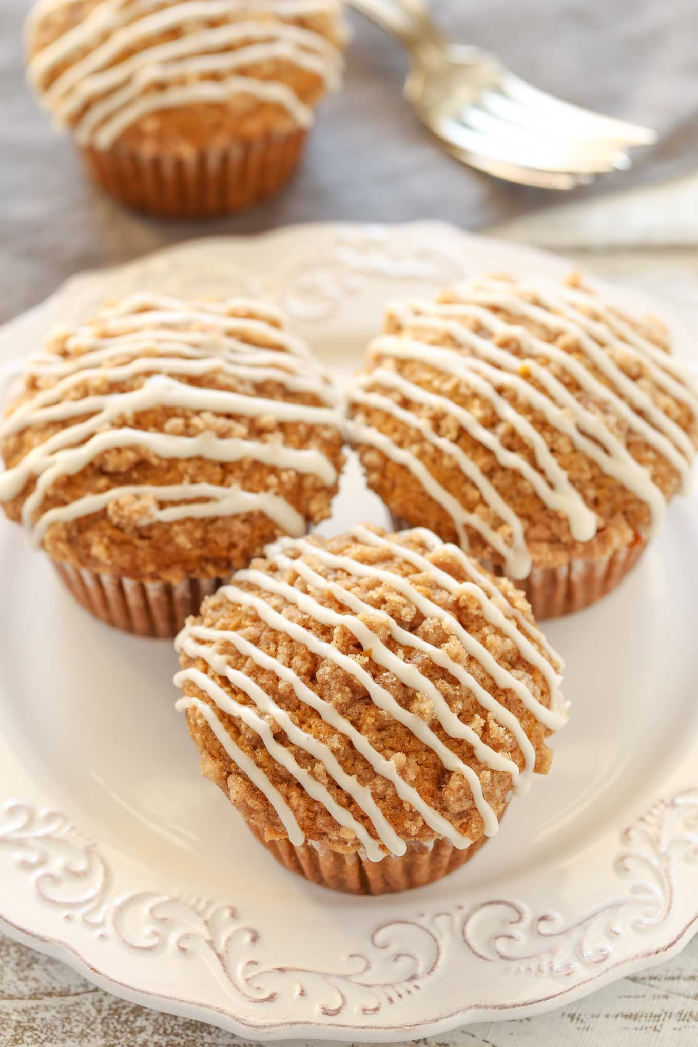 Three glazed pumpkin streusel muffins on a white plate. Another muffin and a fork rest in the background.