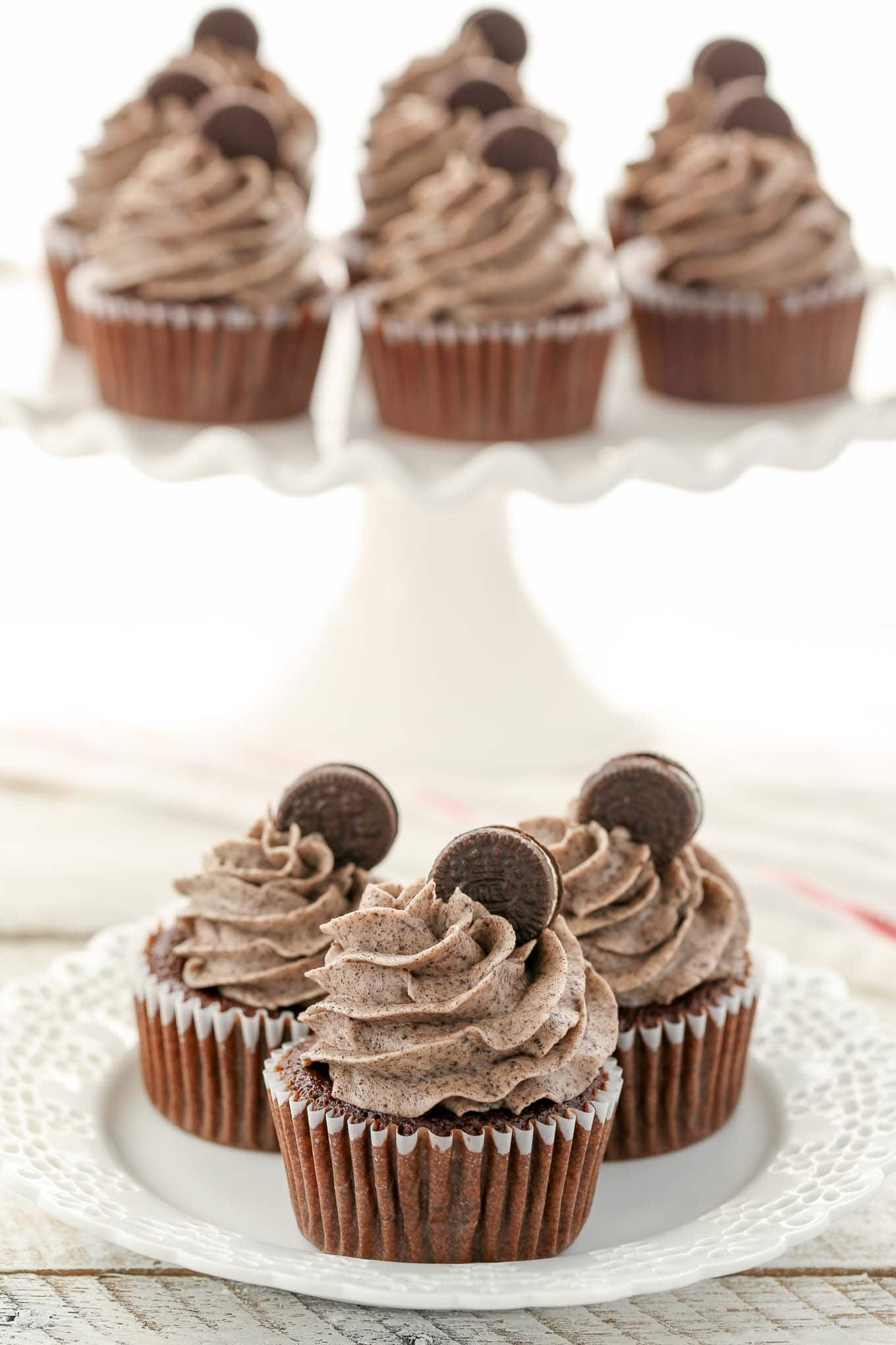 Three oreo cupcakes on a white plate. More cupcakes rest on a cake stand in the background.