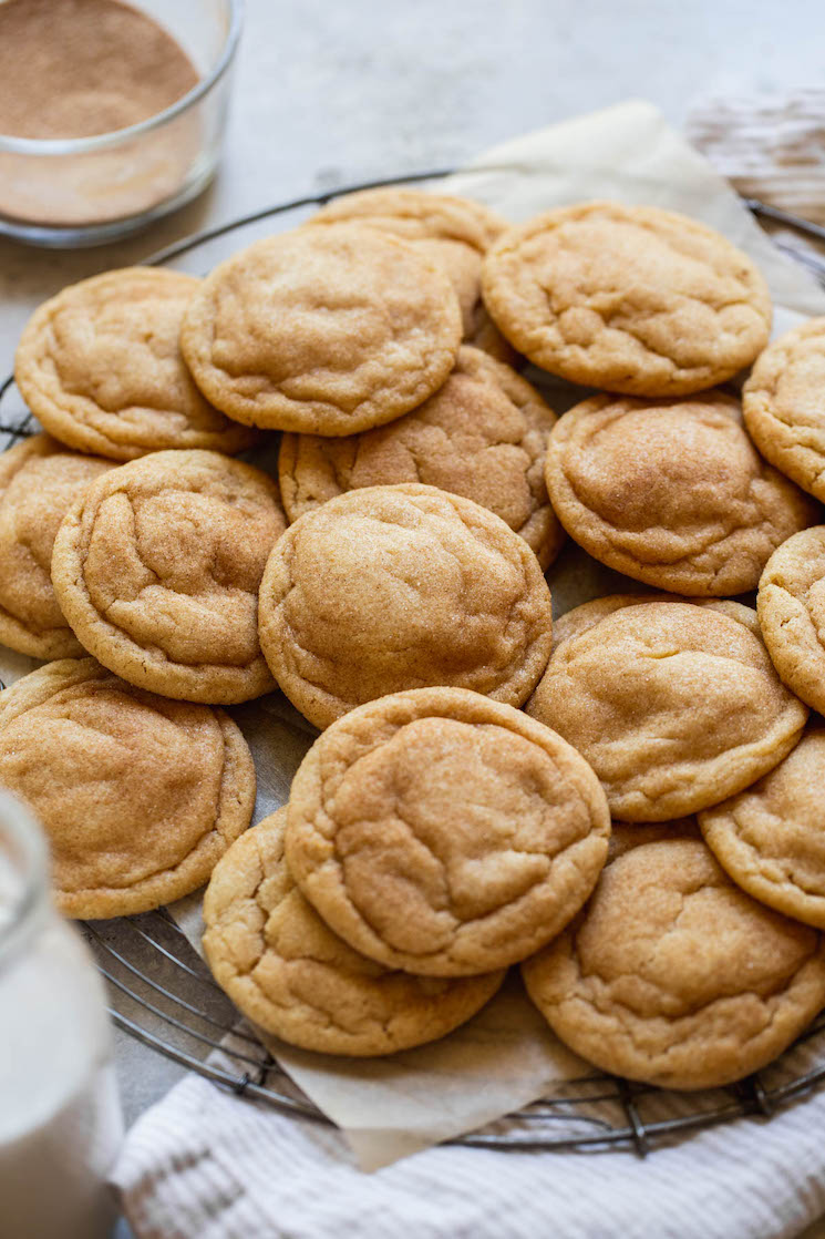 An antique round cooling rack holding a pile of cookies with milk and cinnamon sugar around them.