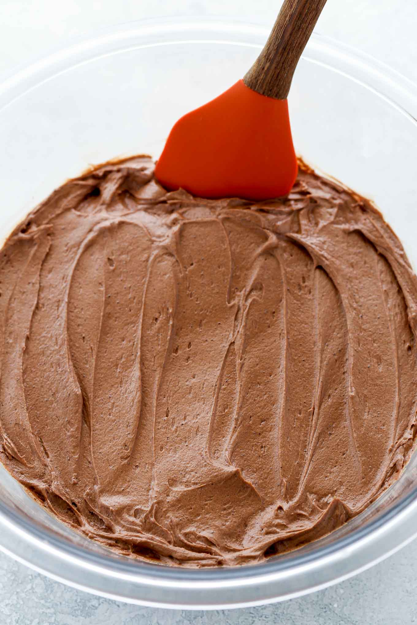 A glass bowl full of chocolate buttercream frosting with a spatula resting on the side.