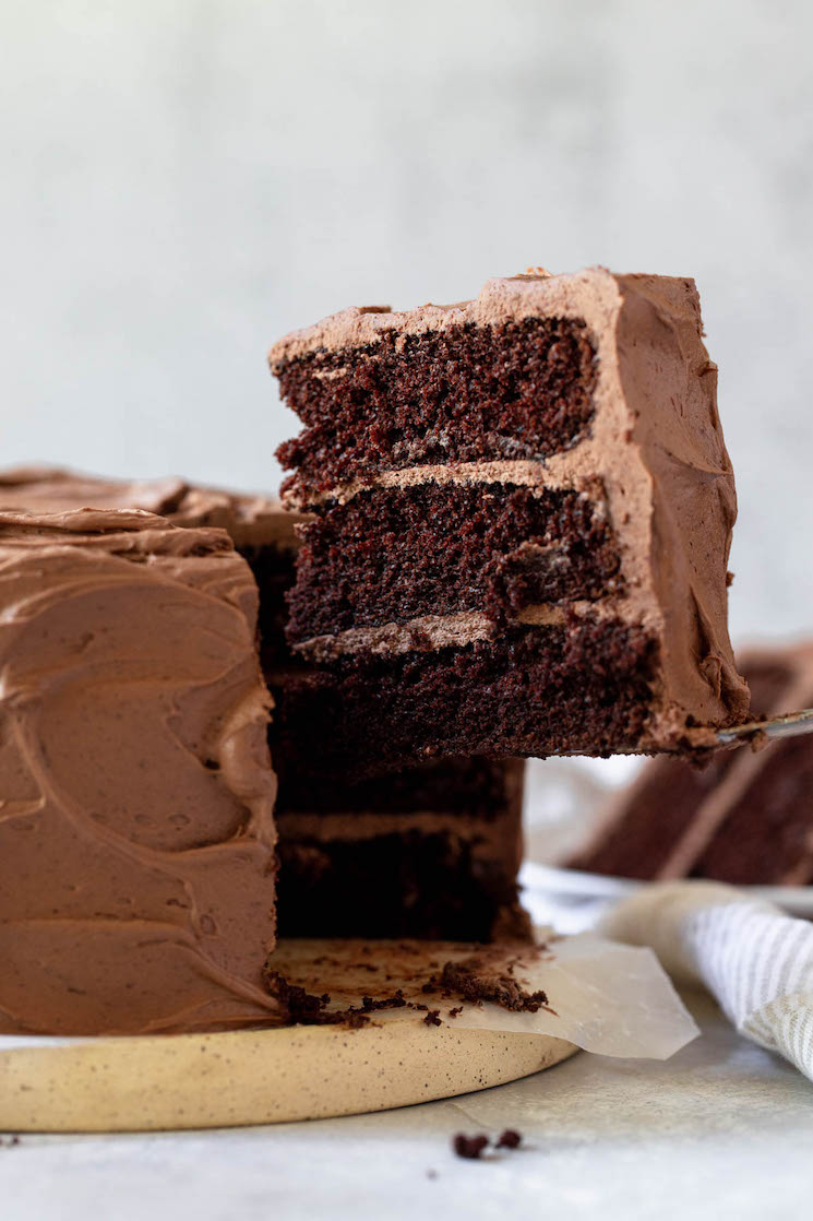 A single piece of a layered chocolate cake being removed showing the different layers.