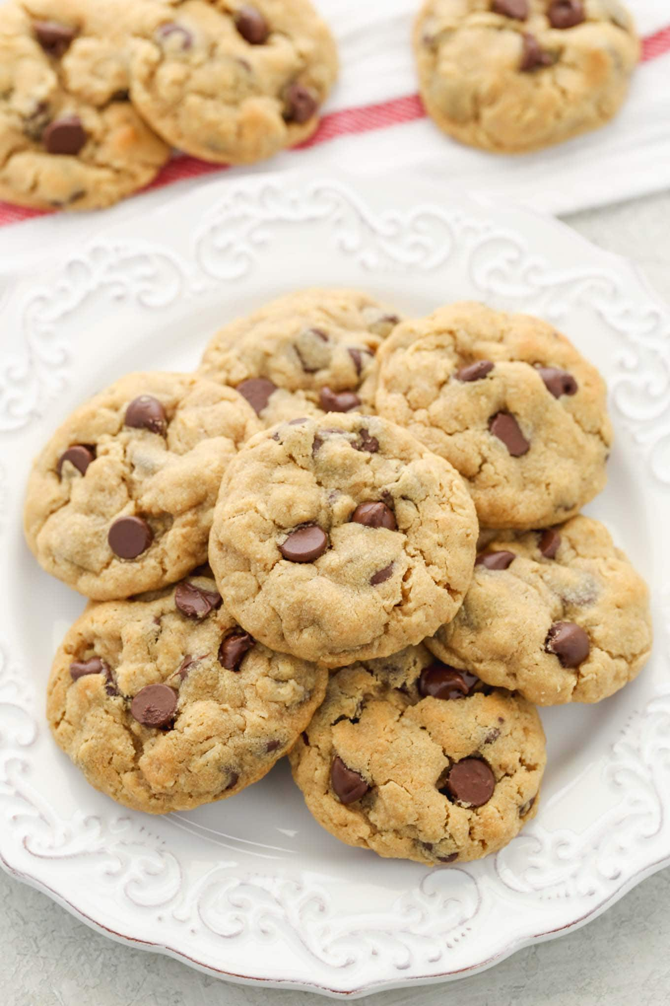 A stack of peanut butter oatmeal chocolate chip cookies on a plate with more cookies in the background.