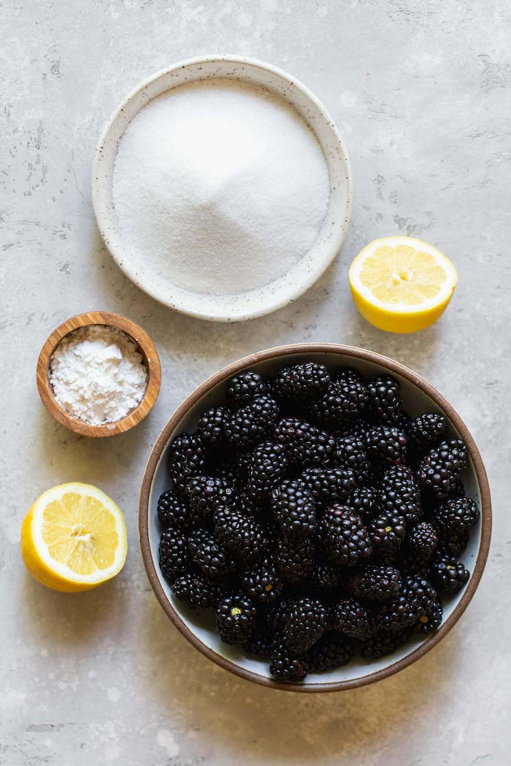 The ingredients for blackberry cobbler filling on a gray surface in rustic bowls.