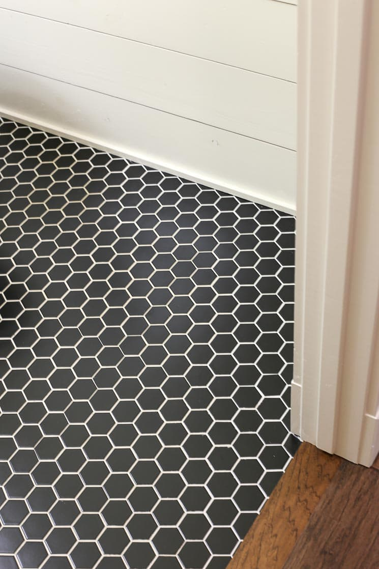 A black hexagon tile floor with white grout and shiplap walls.