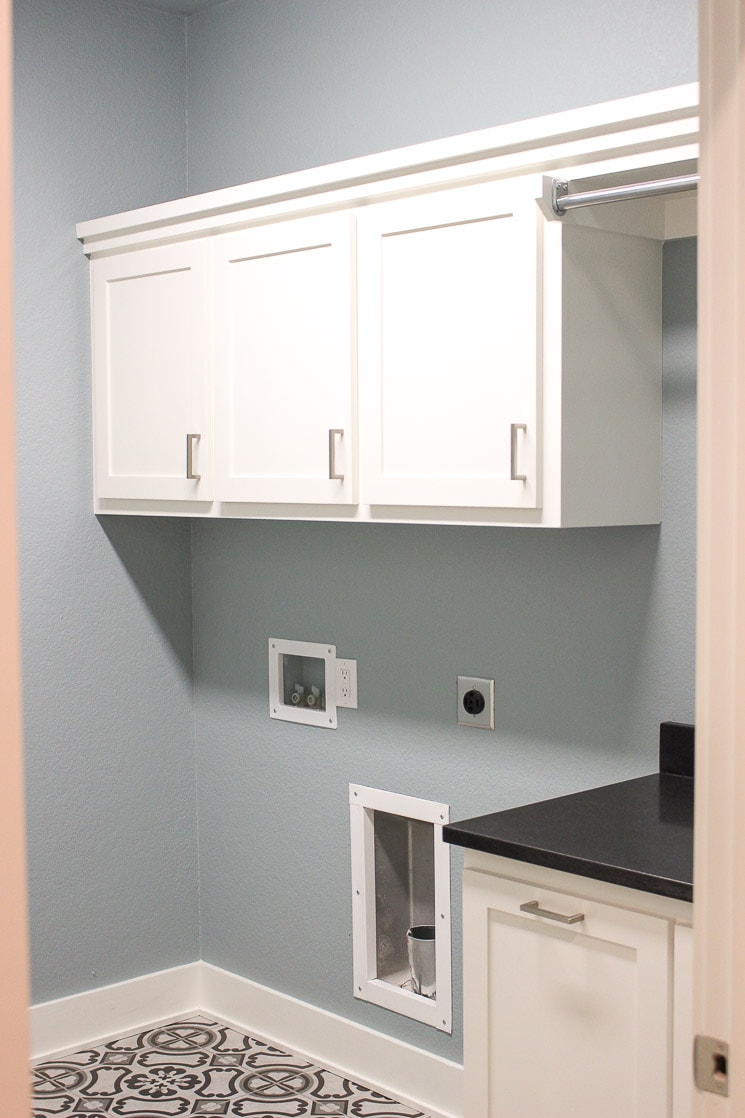 A laundry room with blue walls, white cabinets, and gray tile floor.