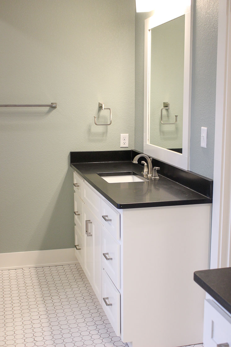 A picture of a bathroom with white tile, white cabinets, and black granite countertops.