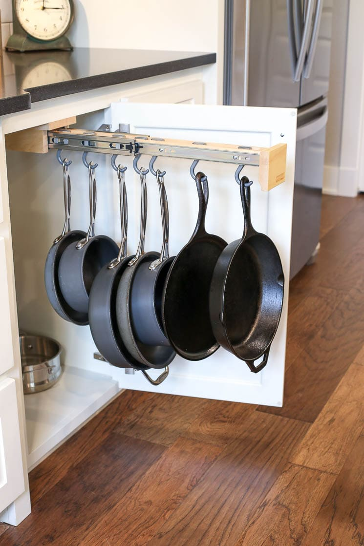 A picture of a pot hanging rack inside of a cabinet.