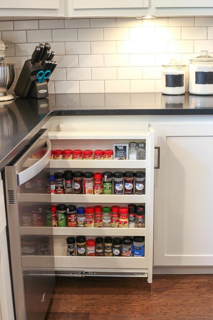 A picture of a spice rack drawer next to a dishwasher.