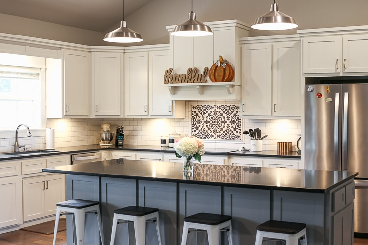 A picture of a kitchen with white cabinets, black countertops, and a gray island.