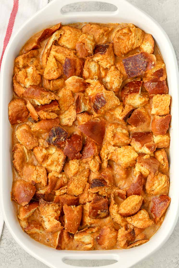Overhead view of unbaked bread pudding in a white baking dish.