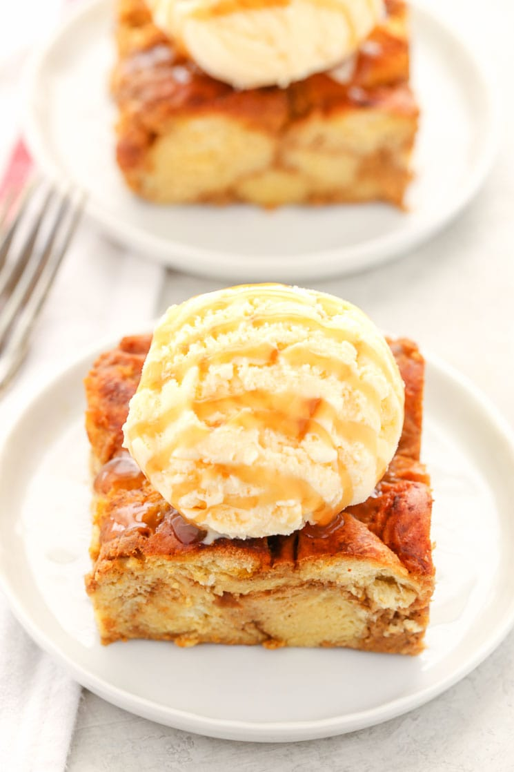 Two slices of pumpkin bread pudding topped with ice cream and caramel sauce on white plates.