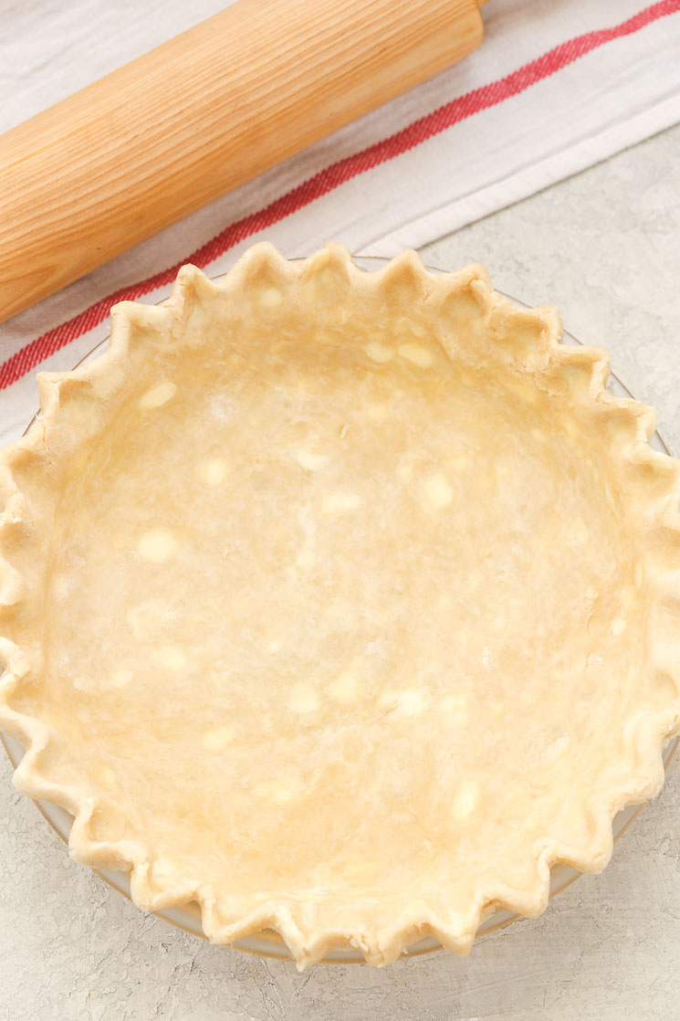A pie crust in a glass pie dish that's ready to be blind baked. A wood rolling pin and striped towel are next to the crust.