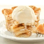 A slice of apple pie with ice cream on top.